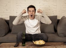 Excited young man sitting on the couch watching football. Sports supporters and fans concept. Lifestyle portrait of excited football fan having fun watching stock photography
