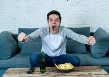 Excited young man sitting on the couch watching football. Sports supporters and fans concept. Lifestyle portrait of excited football fan having fun watching royalty free stock photography