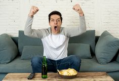 Excited young man sitting on the couch watching football. Sports supporters and fans concept. Lifestyle portrait of excited football fan having fun watching stock photo