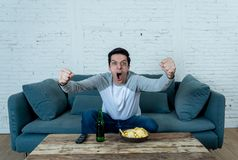 Excited young man sitting on the couch watching football. Sports supporters and fans concept. Lifestyle portrait of excited football fan having fun watching stock image