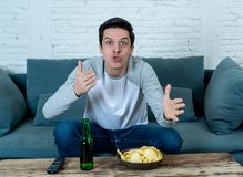 Excited young man sitting on the couch watching football. Sports supporters and fans concept. Lifestyle portrait of excited football fan having fun watching royalty free stock images