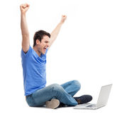 Excited young man using laptop. Young man over white background Royalty Free Stock Photography