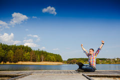 Excited young man using laptop. Excited young man sitting near the lake and using laptop Royalty Free Stock Images