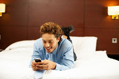 Excited young man waiting for message reply. Messaging with his girlfriend after work Royalty Free Stock Image