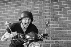 Excited Young Man Wearing Helmet on Motorcycle. Black and White Image of Excited Young Man with Open Mouth Wearing Helmet and Sitting on Motorcycle in front of Royalty Free Stock Photo