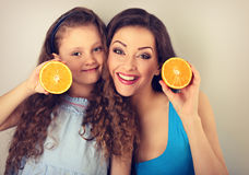 Excited young mother and cute long hair daughter holding slices Royalty Free Stock Photography