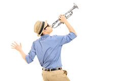 Excited young musician playing trumpet. Isolated on white background, rear view Stock Photo