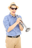 Excited young musician wearing sunglasses and holding a silver t Stock Photo