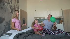 Joyful family playing with balloons on bed stock footage