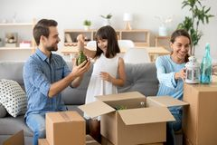 Happy young family unpack boxes moving to new home royalty free stock images