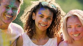 Excited young people with faces covered in colours, friends smiling for camera Royalty Free Stock Image