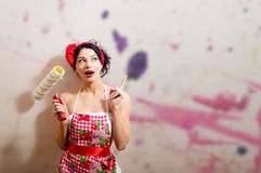 Excited young pin up housewife in apron with paint Stock Photos