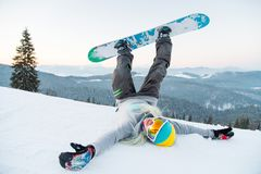Excited young snowboarder woman having fun on the slope lying on the snow with her legs in the air stock photography