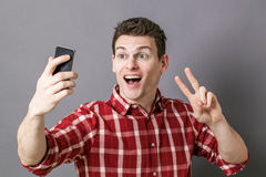 Excited young sportsman making v-sign for victory on selfie Stock Photo