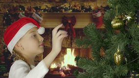 Excited young white girl decorating christmas tree and with happy looking to fir tree. Preparing for Merry Christmas and stock footage