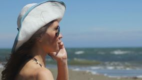 Excited young woman on beach talking emotionally on phone, waving hands, smiling stock footage