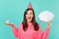 Excited young woman in birthday hat hold in hand cake with candle empty blank Say cloud speech bubble for promotional. Content isolated on blue background stock photo