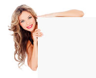 Excited young woman with a blank billboard. Against white background royalty free stock photo