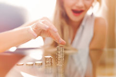 Excited young woman building coin columns on glass desk Stock Photos