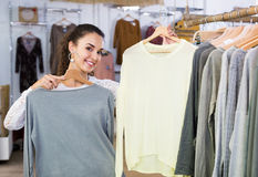 Excited young woman buying pullover Stock Photography