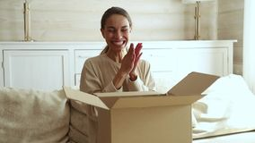 Excited young woman consumer open cardboard box get postal parcel. Happy female customer receive carton package with gift sit on sofa at home satisfied with stock video