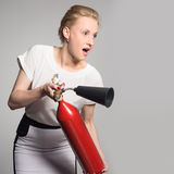 An excited young woman with a fire extinguisher Stock Images