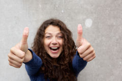 Excited young woman giving thumbs up with both hands Stock Photography