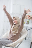 Excited young woman with hijab raise her arm up while sitting on Stock Image