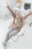 Excited young woman with hijab raise her arm up while sitting on Royalty Free Stock Images