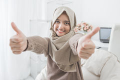 Excited young woman with hijab smiling to camera and showing thu Royalty Free Stock Photography