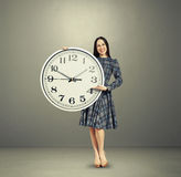 Excited young woman holding big clock Stock Image