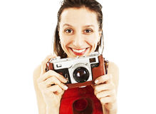 An excited young woman holding a camera in hand. Isolated on white background Stock Photo