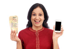 Excited young woman holding Indian currency and mobile phone. Mobile banking Stock Photo