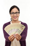 Excited young woman holding Indian currency Royalty Free Stock Images