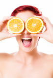 Excited young woman holding oranges over her eyes Royalty Free Stock Photography