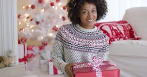 Excited young woman holding up a Christmas gift stock footage
