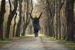 Excited young woman is jumping with arms raised up royalty free stock image