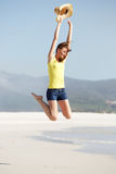 Excited young woman jumping on the beach Royalty Free Stock Photos