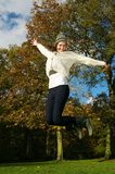Excited young woman jumping outside on a beautiful autumn day Royalty Free Stock Photo