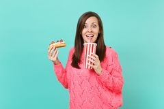 Excited young woman in knitted pink sweater holding in hands eclair cake, plastic cup of cola or soda isolated on blue. Excited young woman in knitted pink stock photos