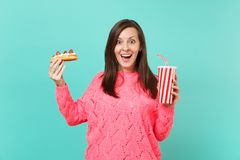 Excited young woman in knitted pink sweater holding in hands eclair cake, plastic cup of cola or soda isolated on blue. Excited young woman in knitted pink stock photography