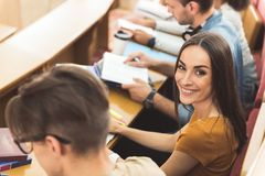 Excited young woman listening to lecture with interest. I like studying at this university. Top view portrait of happy female student looking at camera and Stock Image