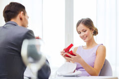 Excited young woman looking at boyfriend with box Stock Photography