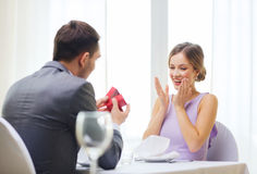 Excited young woman looking at boyfriend with box. Restaurant, couple and holiday concept - excited young women looking at boyfriend with gift box at restaurant Stock Image