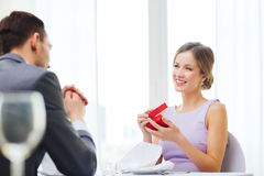 Excited young woman looking at boyfriend with box Stock Photos