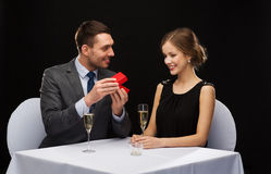 Excited young woman looking at boyfriend with box. Restaurant, couple and holiday concept - excited young women looking at boyfriend with gift box at restaurant Royalty Free Stock Images