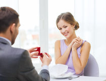 Excited young woman looking at boyfriend with ring Stock Photo