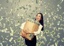 Excited young woman with money. Excited young businesswoman standing under dollar's rain and holding big paper bag with money Stock Image