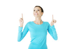 Excited young woman pointing on copy space Royalty Free Stock Photos