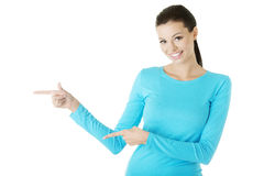 Excited young woman pointing on copy space Royalty Free Stock Image